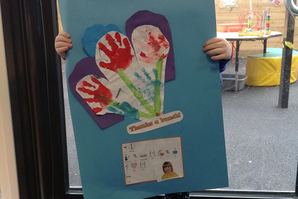 Year 2 pupil showing her handprint flowers