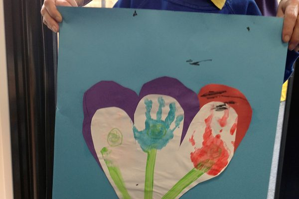 Pupil showing their handprint picture